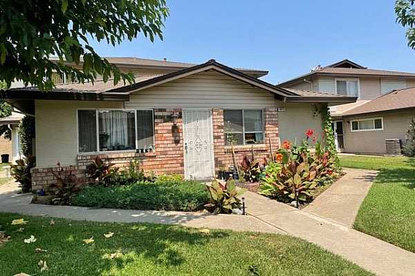 Photo #1 Front of property with nice natural light and small garden area in front