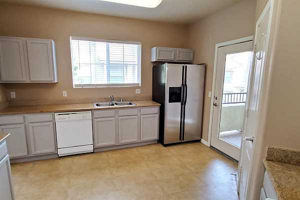Photo #7 Kitchen with updated cabinets and stainless steel appliances. Access to covered patio.