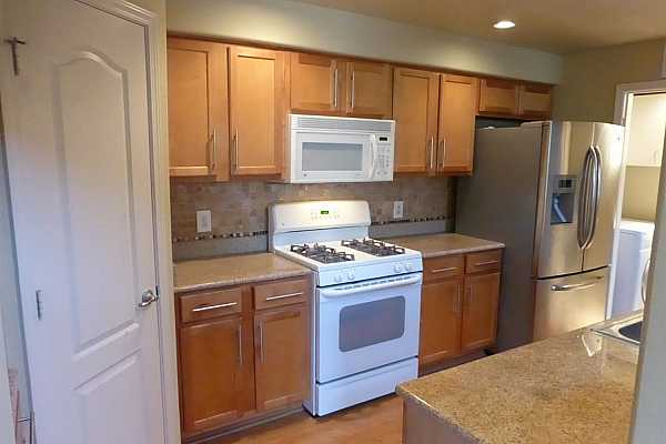 Photo #7 The kitchen features granite counters nice tile backsplash.