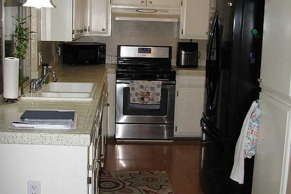 Photo #4 This kitchen has tile counter tops, a gas range and refrigerator included.