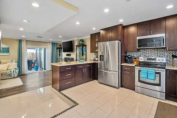 Photo #2 Beautiful Granite Counters, Gorgeous Quartz floors and Stainless Steel Appliances reflect the recessed lighting!