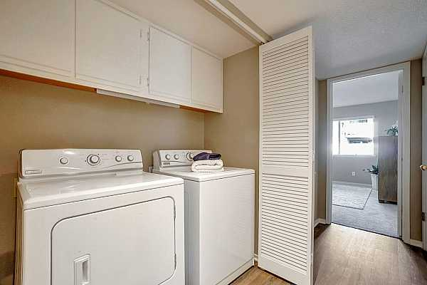 Photo #7 Louvered doors in the hallway houses the laundry with upper cabinets.  The washer/dryer are meant to transfer with the property.