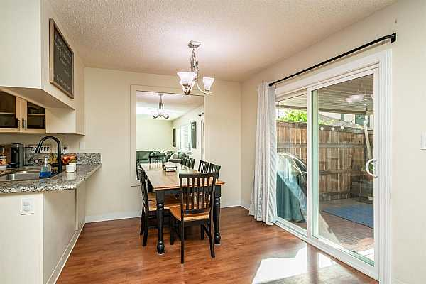 Photo #8 Newer sliding glass door to private patio. Eating bar area and cozy dining room.